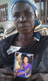 Mother holds picture of her missing daughter.