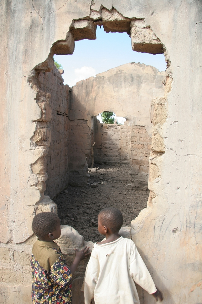Two boys look through a hole in the wall of a house in their village in Nigeria, the ruins a result of Islamic extremism.