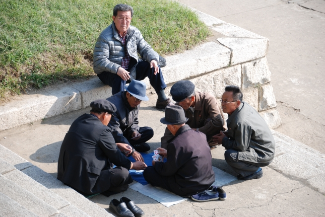 Men playing cards in the street.