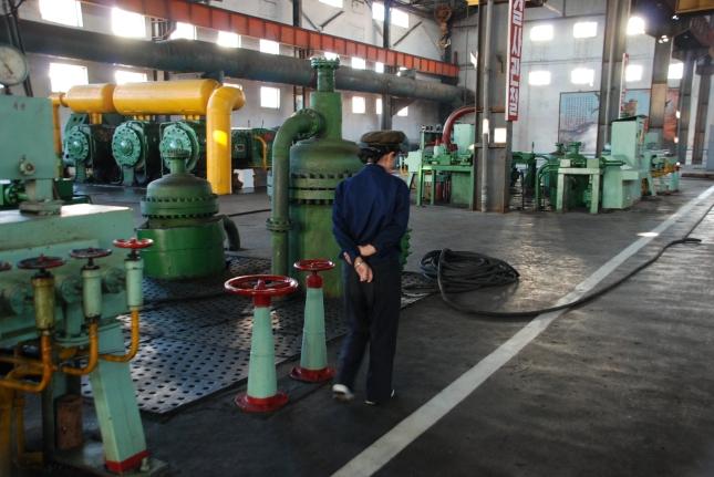 Uniformed woman patrolling a factory.