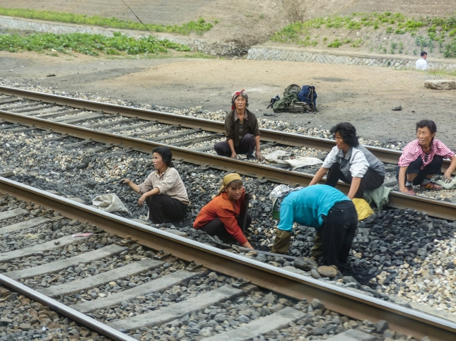 Women replacing wooden railway sleeps with concrete sleepers, digging with their bare hands.