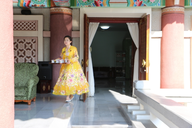 Woman bringing drinks in traditional clothing.