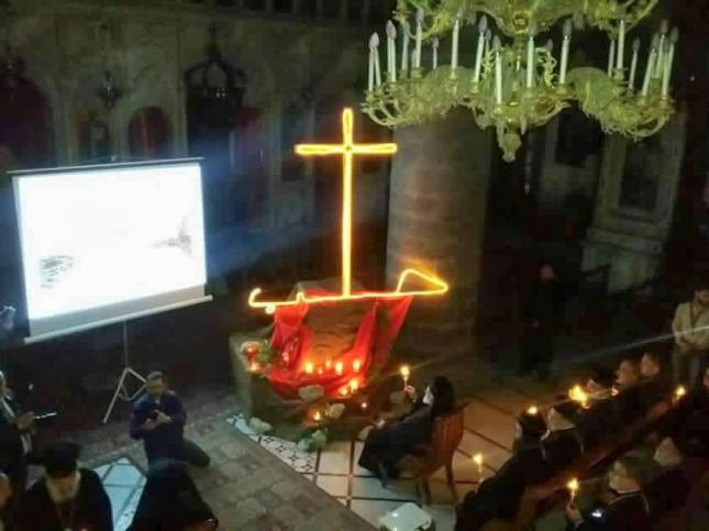 Syrian Christians gather on Sunday 8 may for prayer. The sign says 'Halab', the original name of the city, with the cross forming the letter 'L'.
