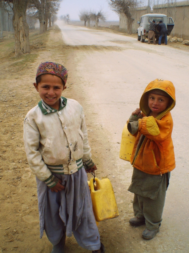 Boys collecting water on the streets of Afghanistan. Date: 2003