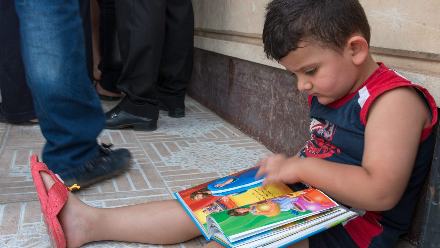 When this boy received his Bible and sticker book, he sat down straight away and started reading.