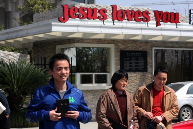 Man holds a Bible in front of a church in Hangzhou, China.