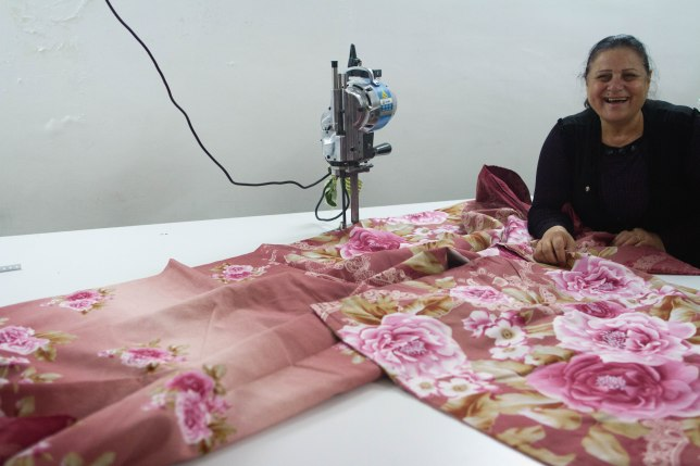 Suaad at the fabric cutting table.