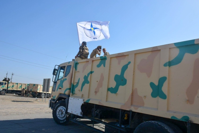 An army truck heading for liberated Qaraqosh waves the Assyrian Christian flag.