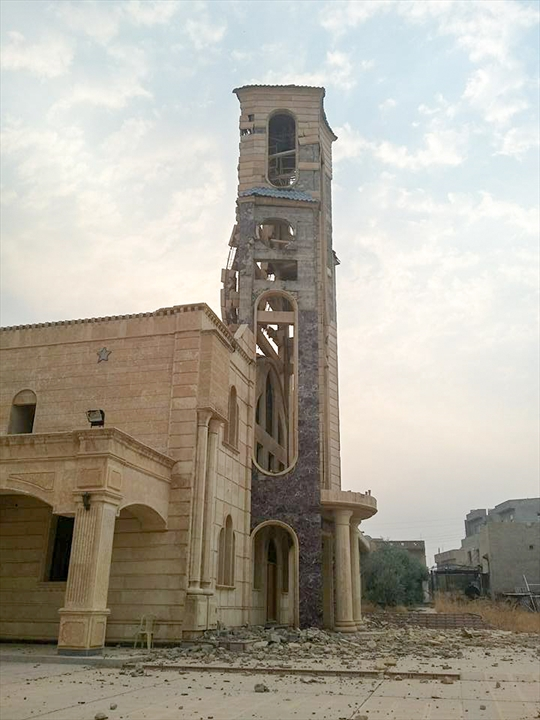 A church tower looks ready to collapse in Qaraqosh.