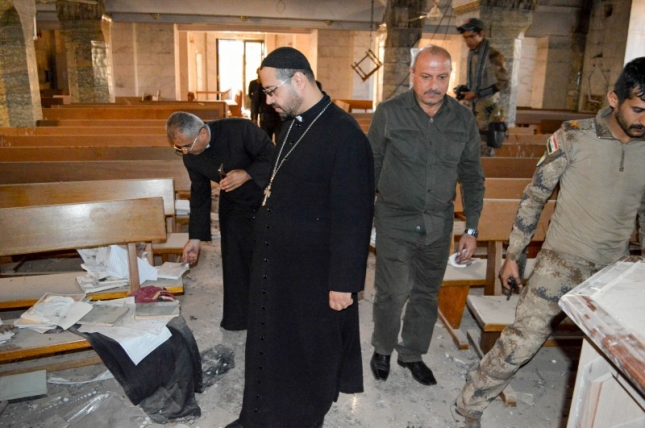 Father Yacoub looks at the destruction inside his church.