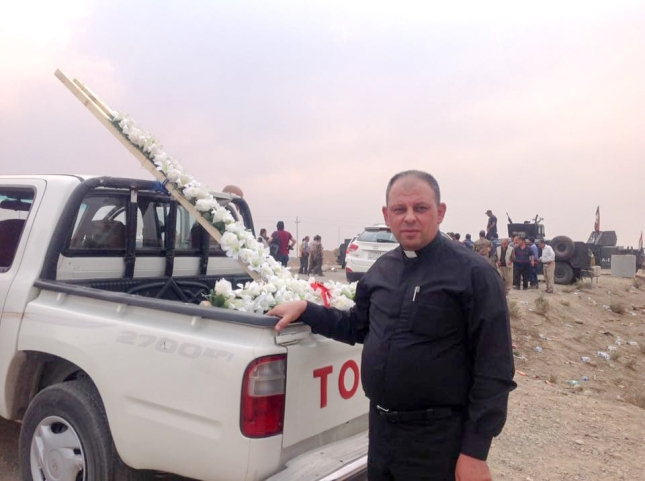 Father Thabet brought a man-high cross covered with flowers that his congregation made in Erbil. He brought it back to their home town, Karamles to put on the Saint Barbara Hill. The one that had been there was taken down by Islamic State.