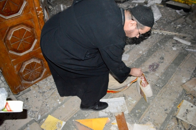Father Yacound picks up a Bible of the floor.