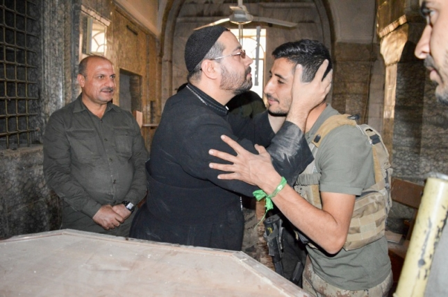 Father Yacoub thanks a soldier for his help liberating the town and church of Bartella.