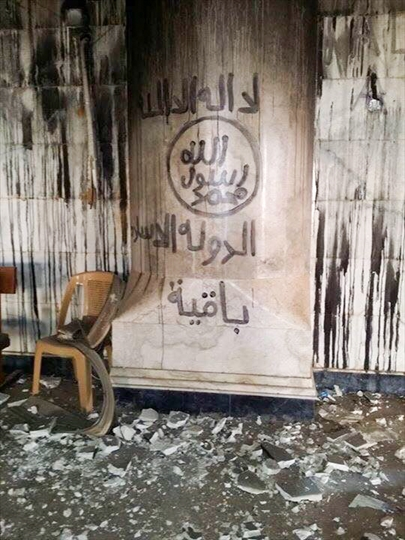 "Islamic State flag spray painted on the wall inside Tahira church. ""There is no god but Allah"" in circle: ""Mohammad is the messenger of Allah"" The text underneath is not on the IS flag, but extra line saying: ""The Islamic State will remain"""