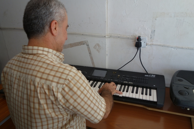 Amer playing piano in his new music shop.